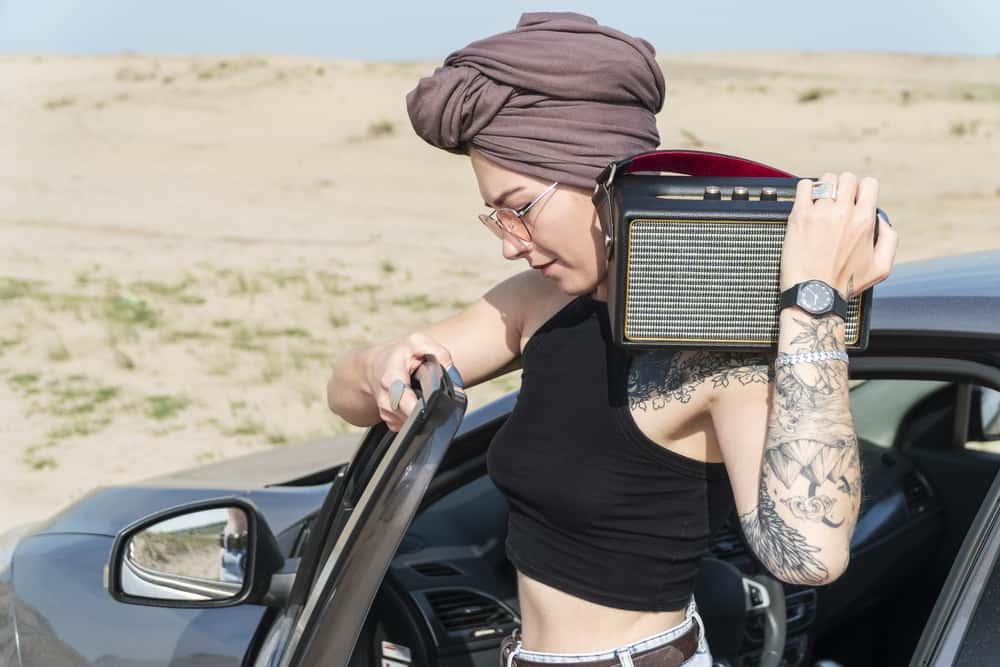 Woman with waterproof speakers on a shoulder